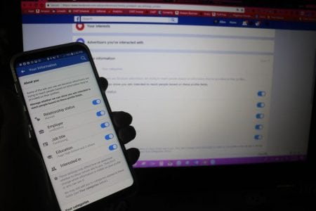 A mobile phone shows a settings page from a Facebook app. The phone is held in front of a computer screen showing a similar page from the Facebook website.