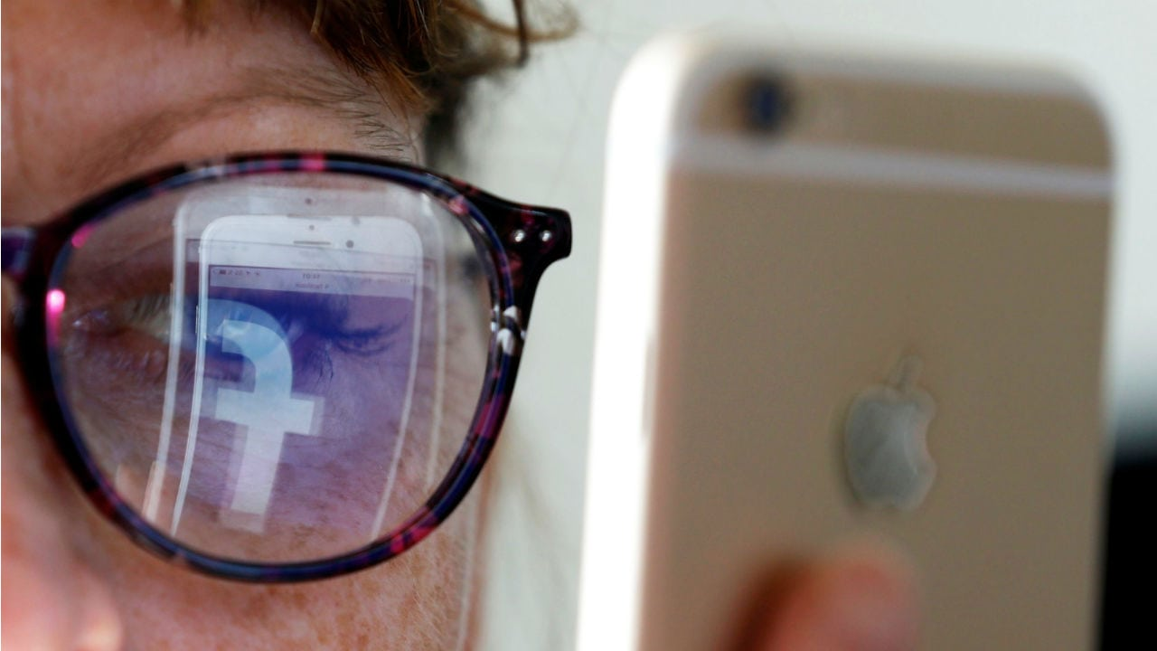 Reflection of the Facebook logo on a woman's spectacles. Image: Reuters