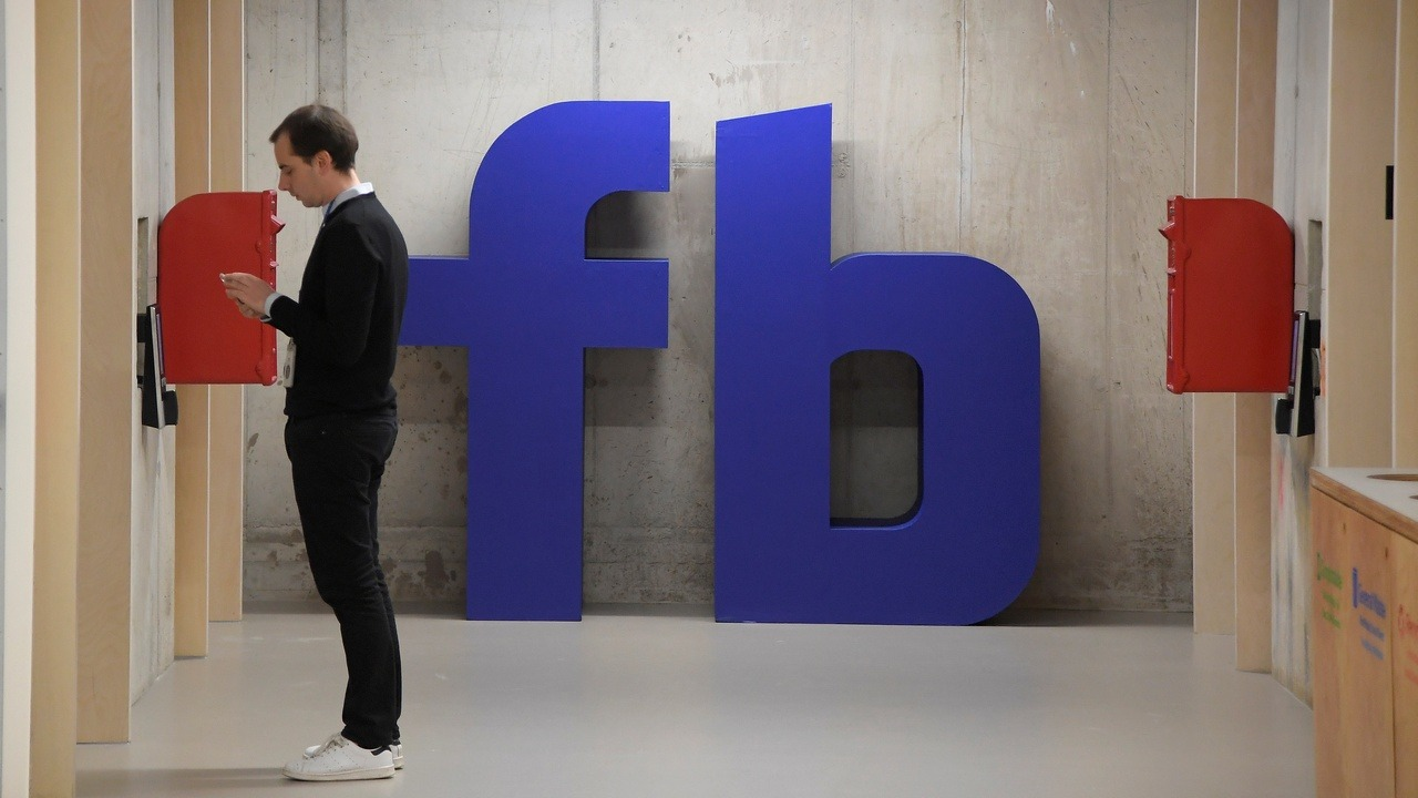 A man waits for an elevator in front of a Facebook logo. Image: Reuters