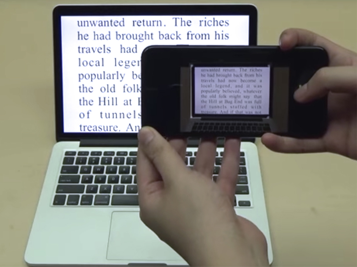 Someone taking a photograph of text on a computer.