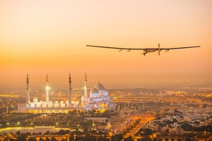 The Solar Impulse 2, a solar-powered plane, flies over the Sheikh Zayed Grand Mosque in Abu Dhabi