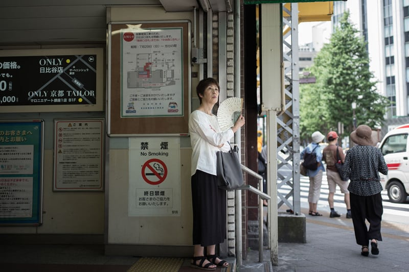 A woman uses a fan as she stands along a street in Tokyo today