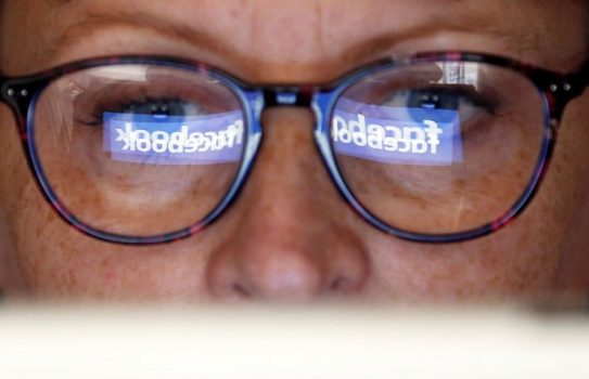 Facebook logo reflects in someone's glasses