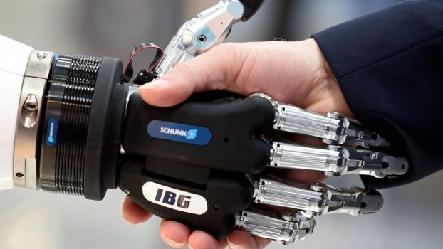 A visitor shakes hands with a humanoid robot at the booth of IBG at Hannover Messe, the trade fair in Hanover, Germany, April 23, 2018. REUTERS/Fabian Bimmer - RC19FE153DE0