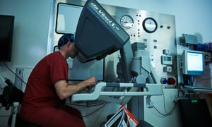 Greg Shaw controls the robot as it operates on a patient