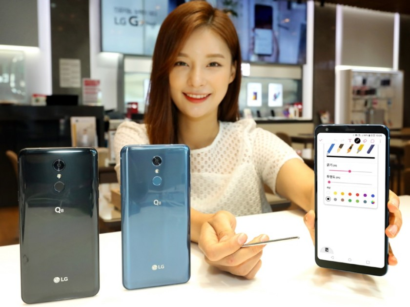 An image of a Korean woman holding the 2018 version of the LG Q8.