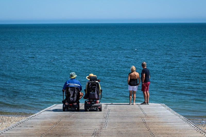 Couples look out to sea from Selsey Beach in Chichester during the hottest day of the year so far on Monday 23rd July