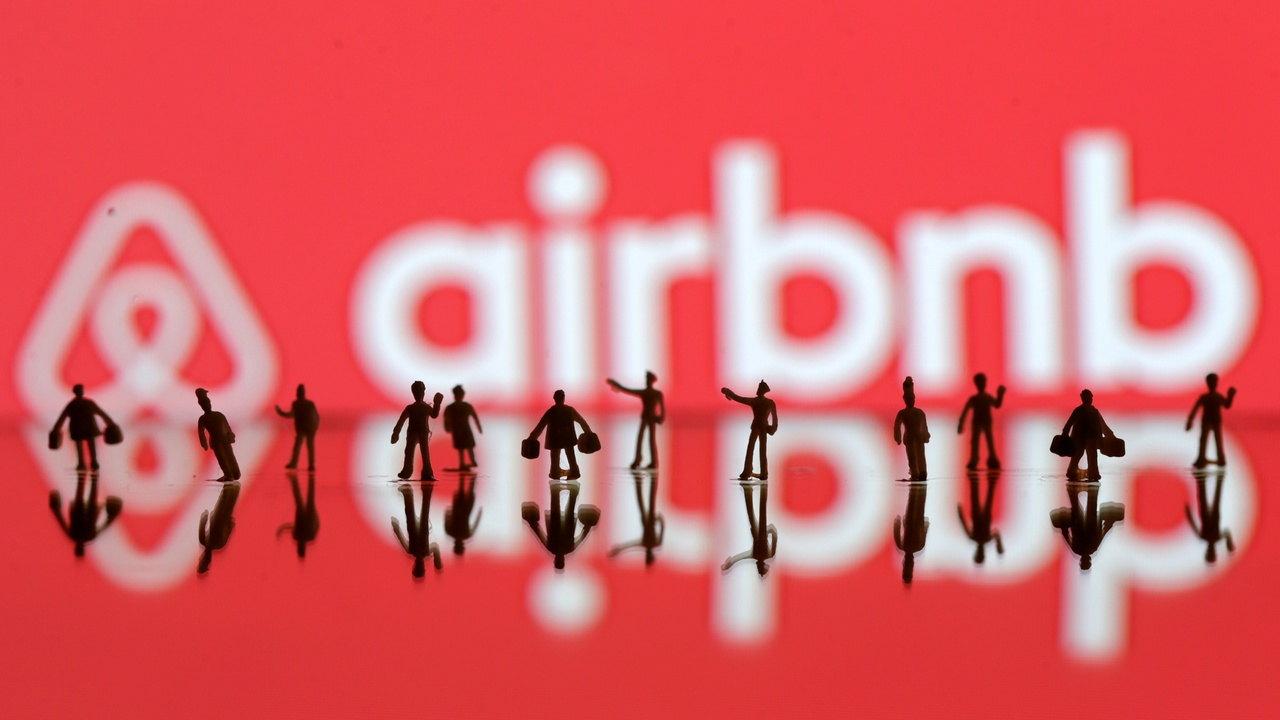 A 3D printed people's models displayed in front of Airbnb logo. Image: Reuters