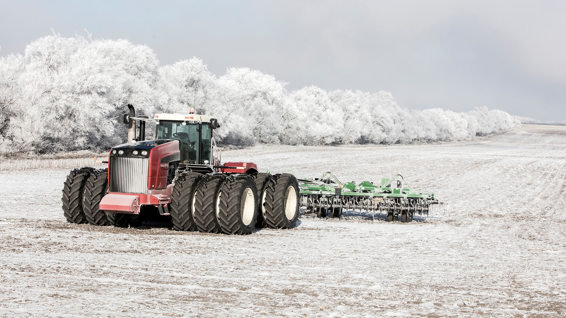 A combine harvester moving on a snow-covered field
