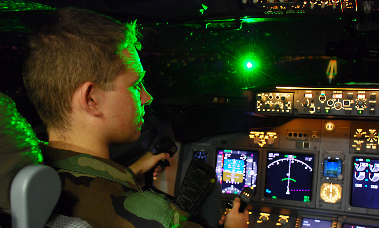 Air Force 2nd Lt. Paul LaTour is illuminated by a brilliant flash of green laser light during a simulated landing in a Boeing 737 flight simulator at the FAA's Mike Monroney Aeronautical Center in Oklahoma City, Okla.